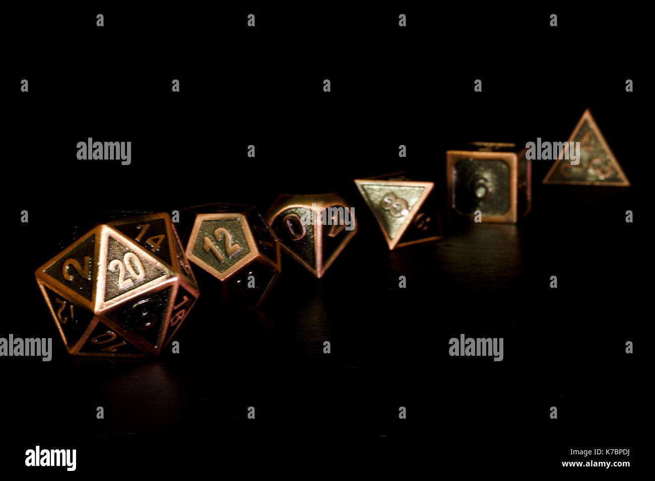 A set of polyhedral dice on a slate surface. These dice are used for role playing games such as Dungeons & Dragons. Stock Photo