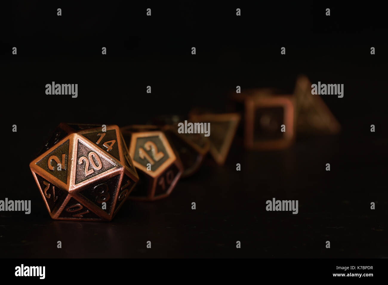 A set of polyhedral dice on a slate surface. These dice are used for role playing games such as Dungeons & Dragons. - Stock Image