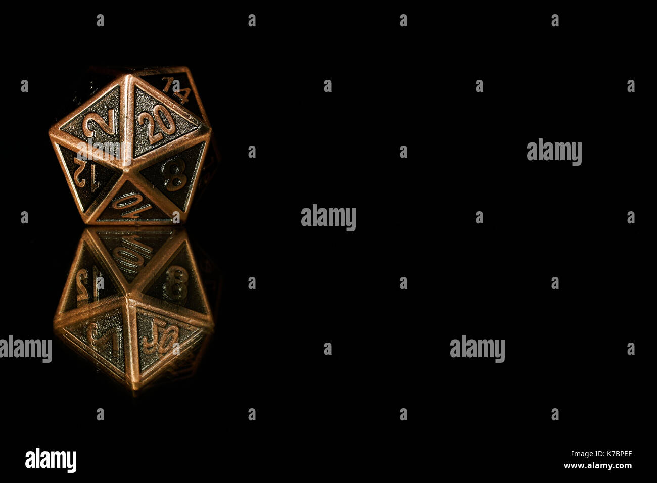 A twenty sided  polyhedral die on a mirrored surface. These type of dice are used for role playing games such as Dungeons & Dragons. - Stock Image