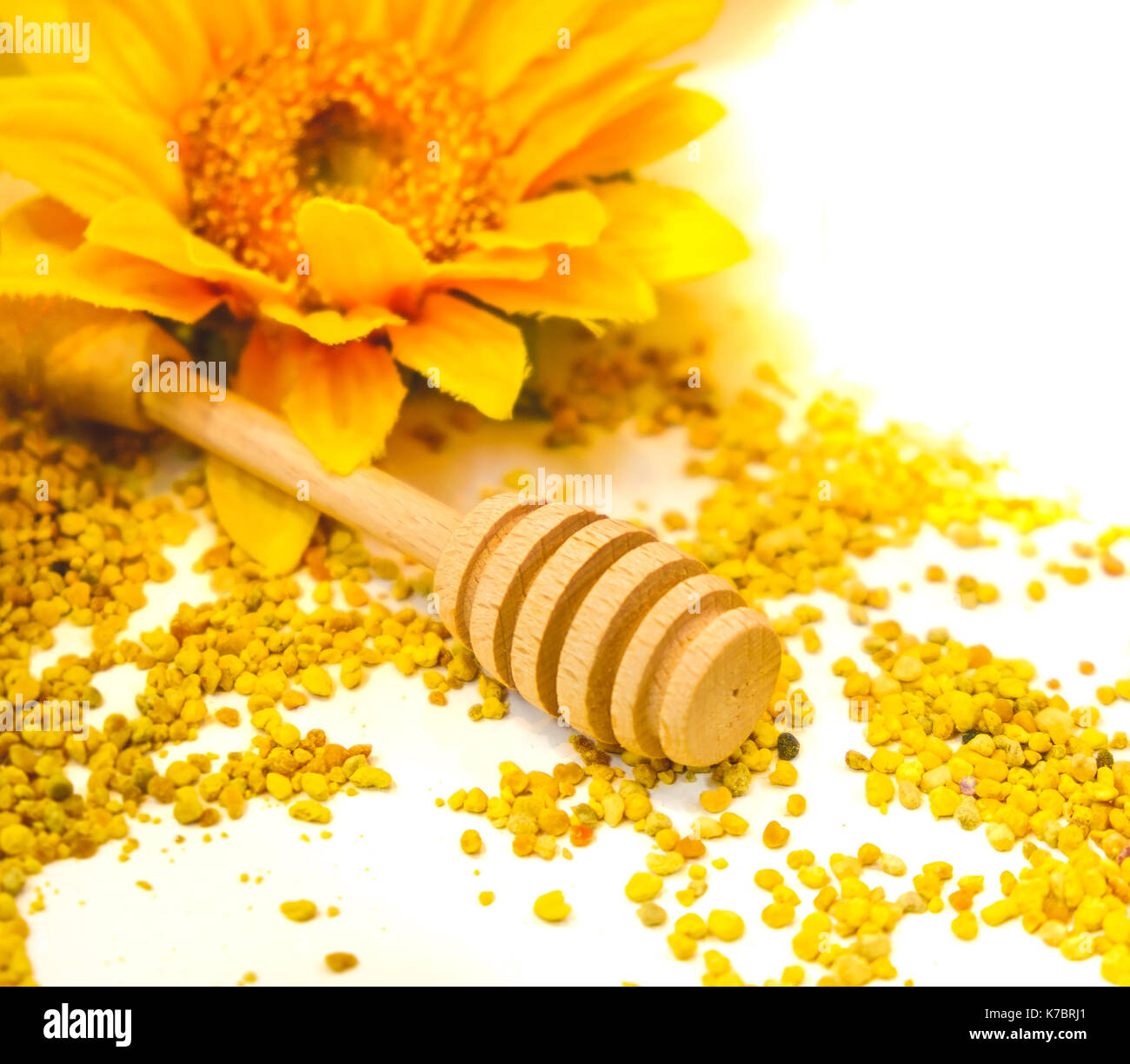 propolis granules honey dripper background drizzle wooden spoon - Stock Image