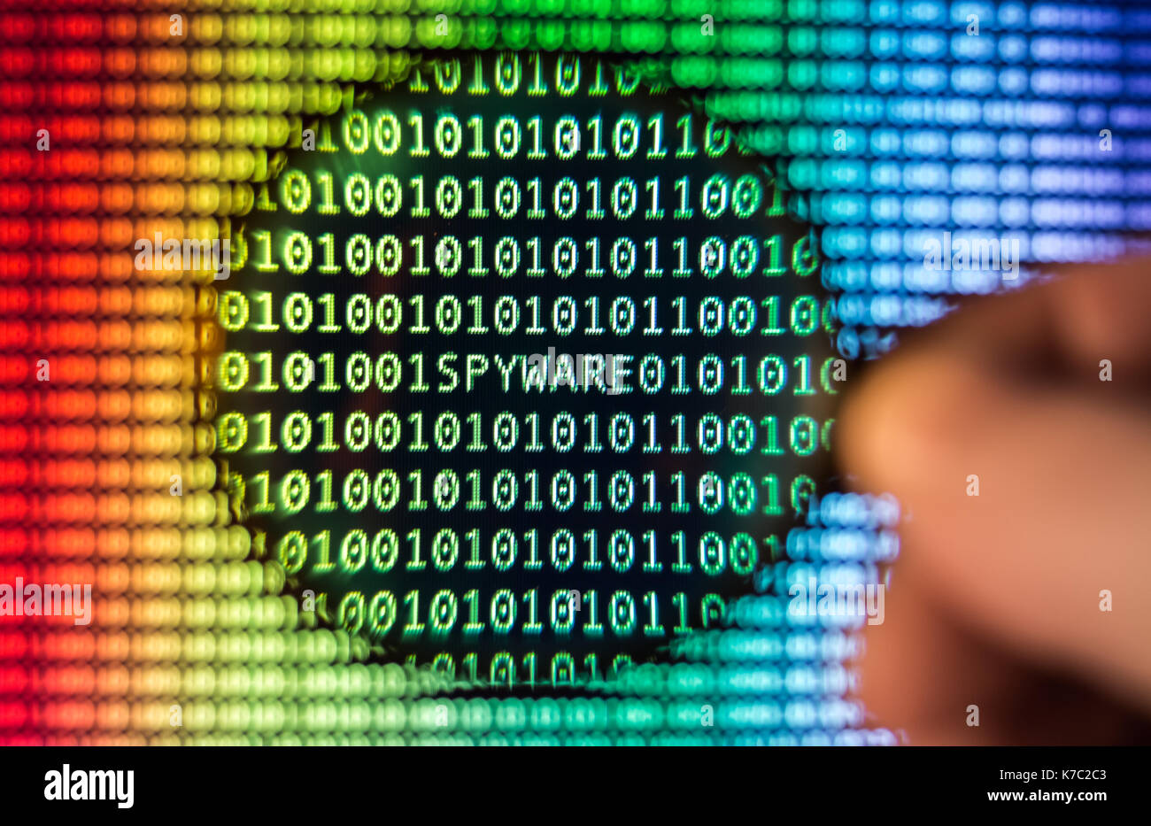 Binary code, Magnifying glass shows spyware, toned - Stock Image