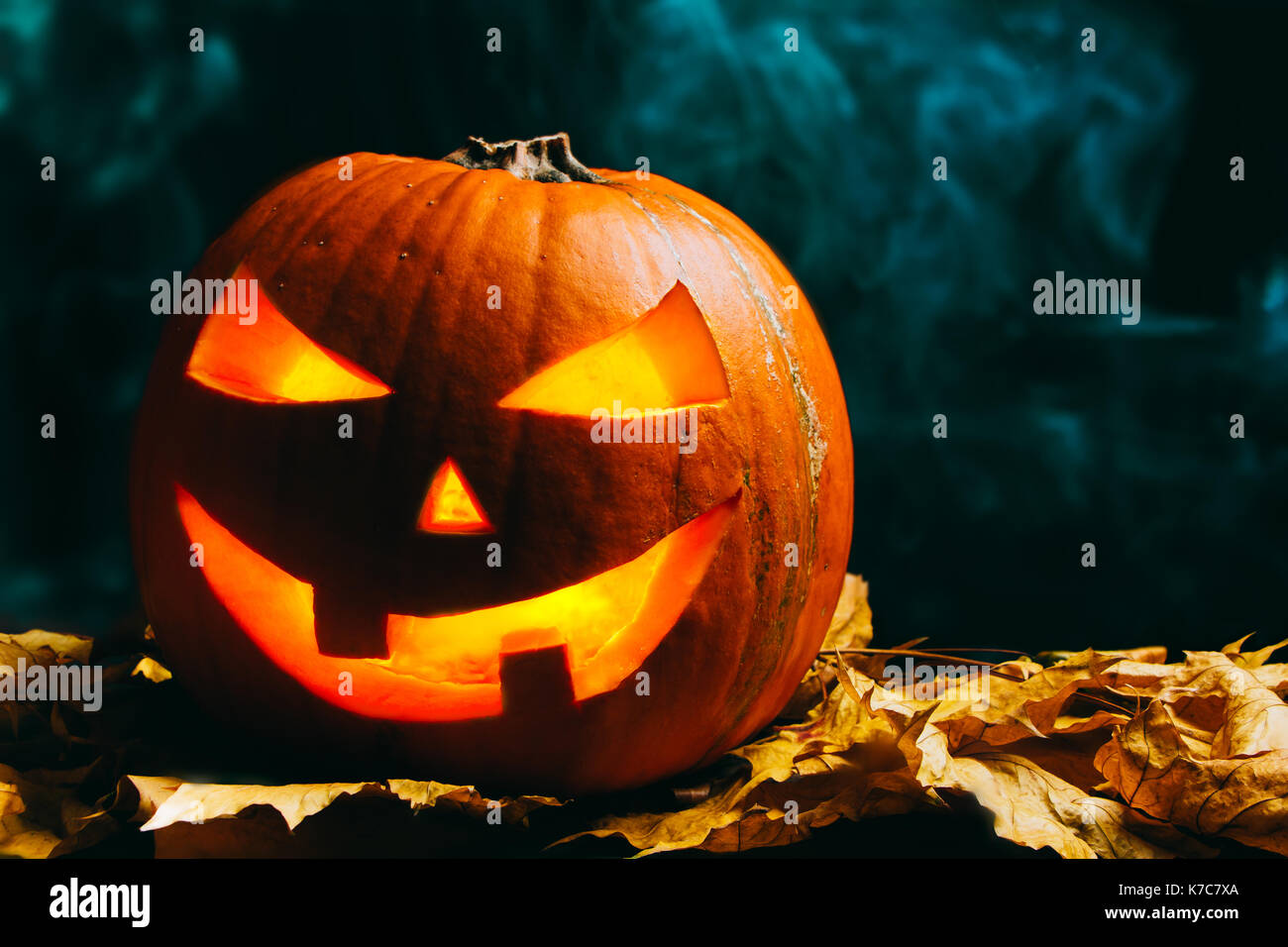Halloween pumpkin lantern with dry leaves on a smoky dark background Stock Photo