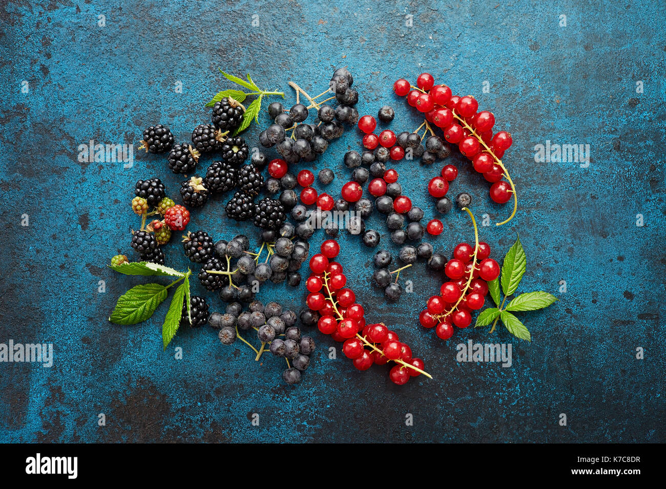 Assorted fresh berries with leaves on metal background. Mix of fresh berries with leaves on textured metal background. - Stock Image