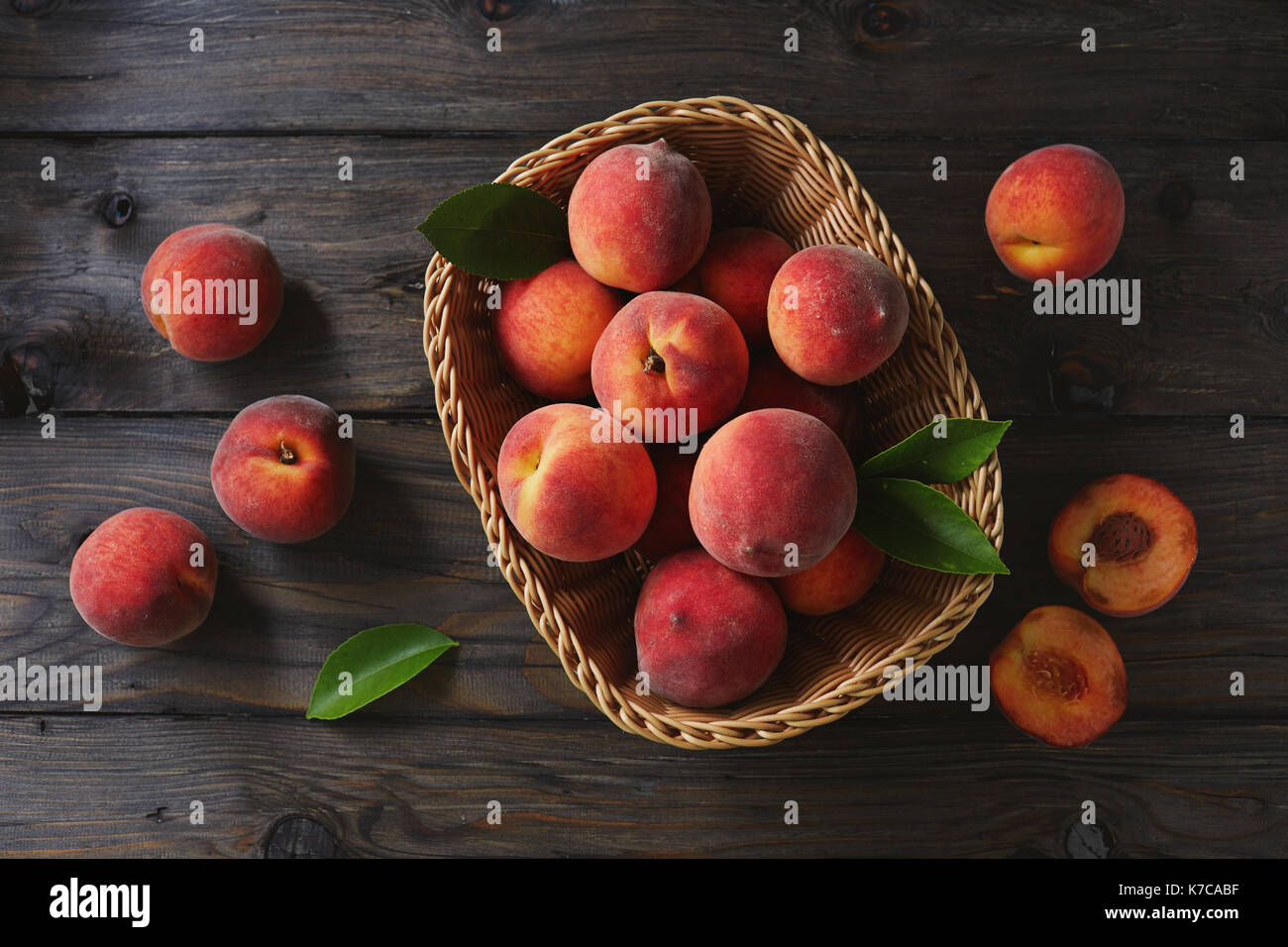 Basket of fresh peaches on a wooden table - Stock Image