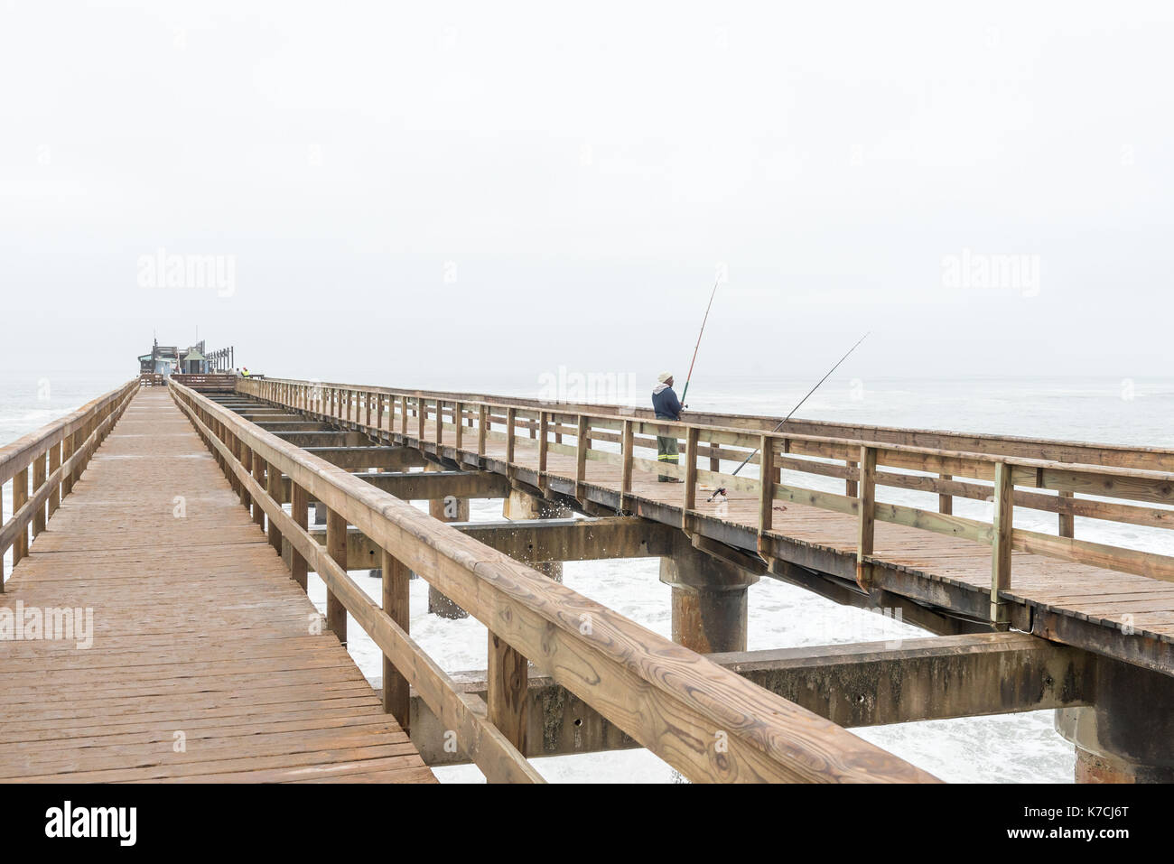 SWAKOPMUND, NAMIBIA - JUNE 30, 2017: An angler on the historic jetty, with a restaurant on its far end, in Swakopmund Stock Photo