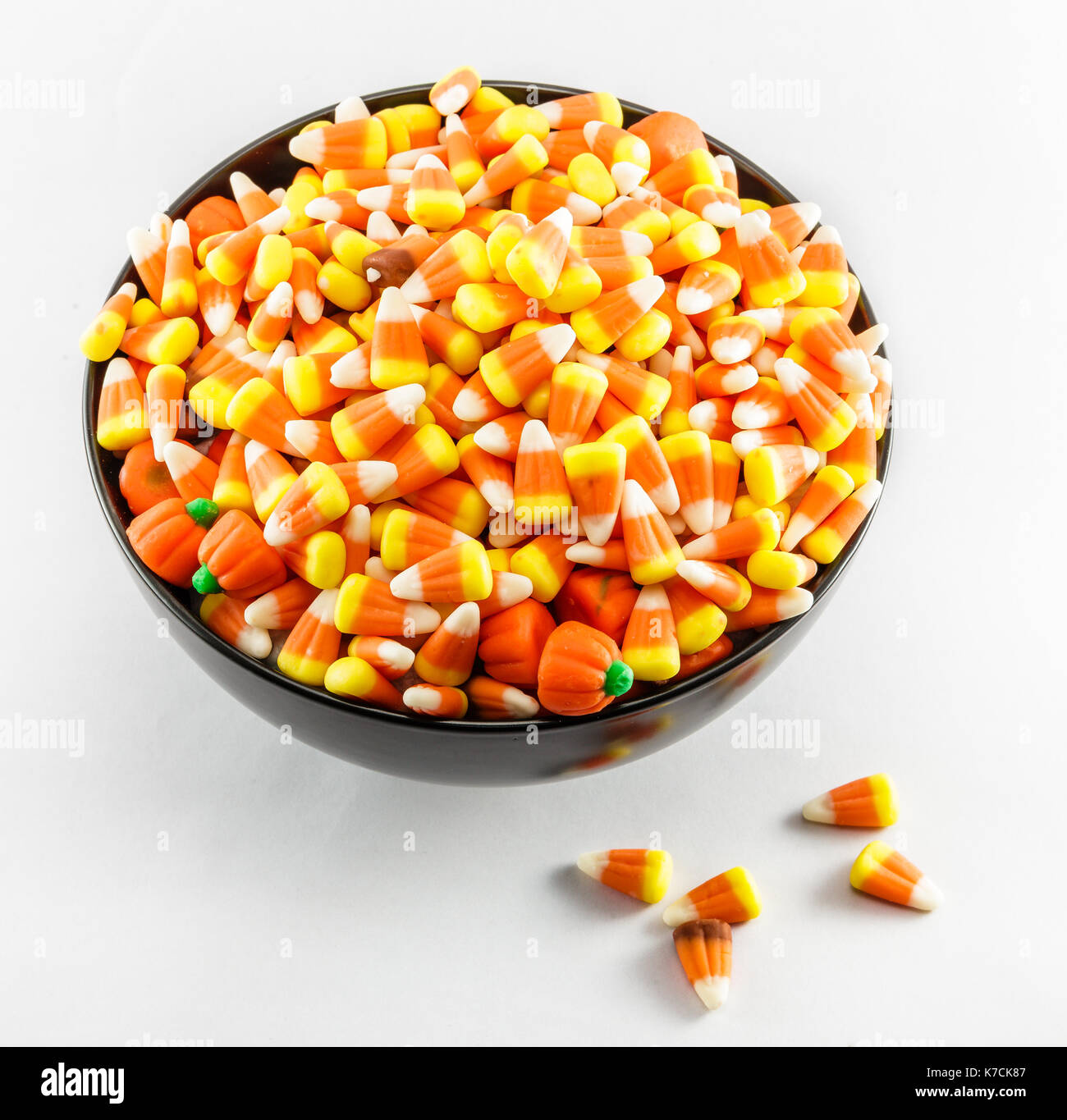A black bowl over filled with Candy Corn taken on a white background. - Stock Image