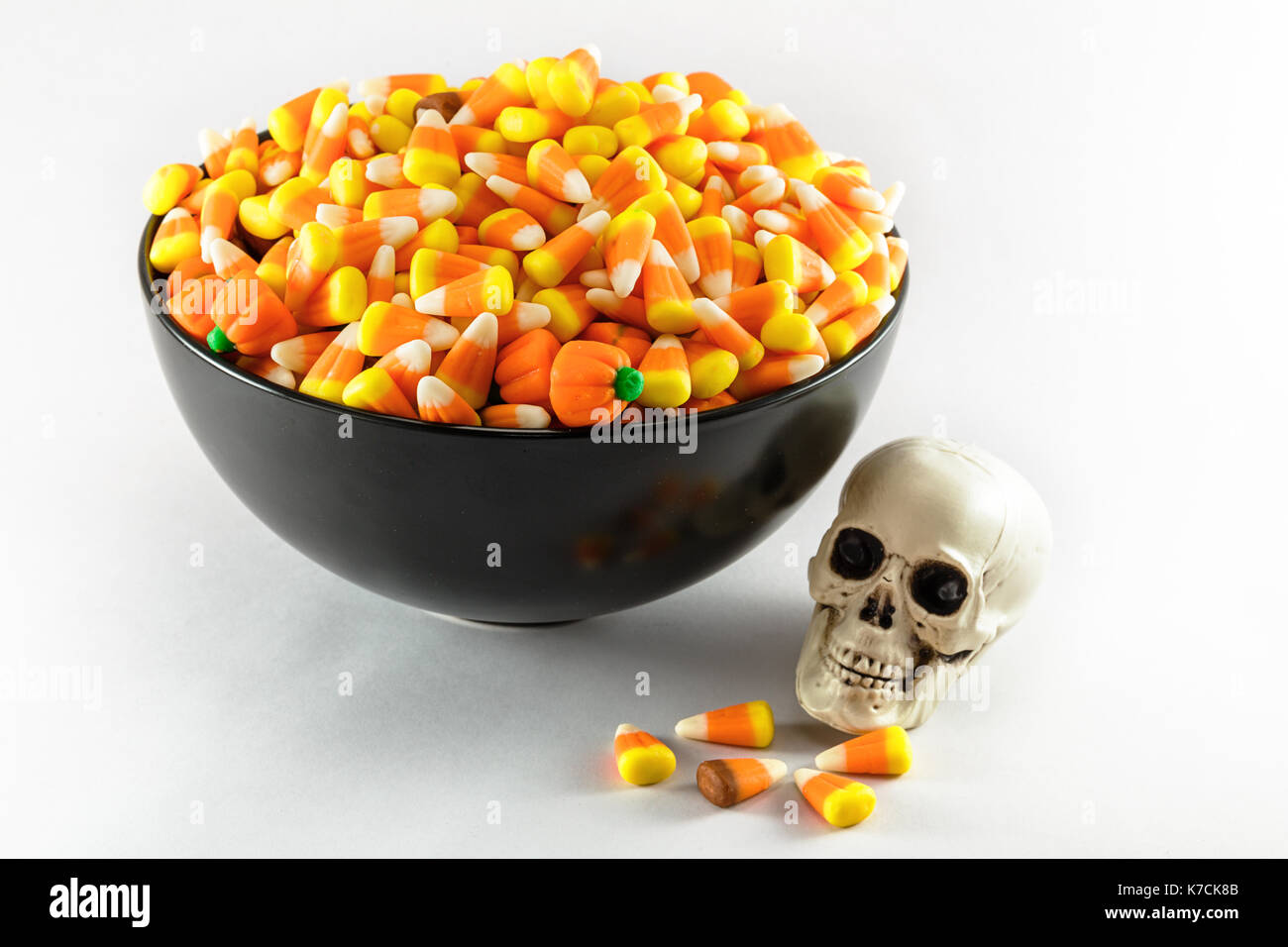 A black bowl over filled with Candy Corn taken on a white background.  A plastic toy skull is also shown in the photo - Stock Image