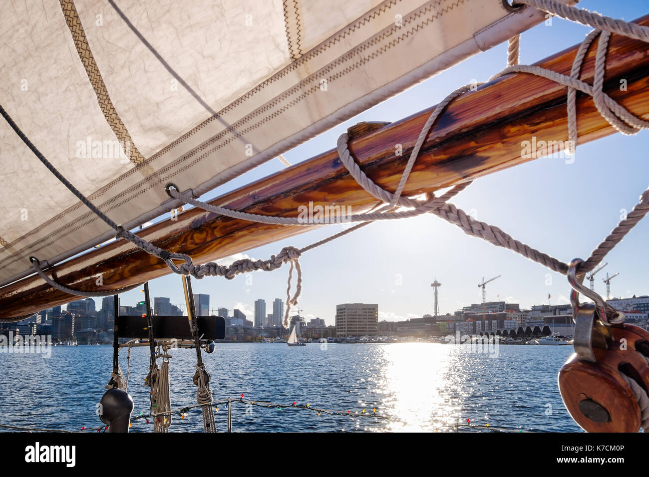Seattle sailing on Lake Union in a vintage yacht, sailboat. Sail frames a view of the skyline and waterfront, including Space Needle. - Stock Image