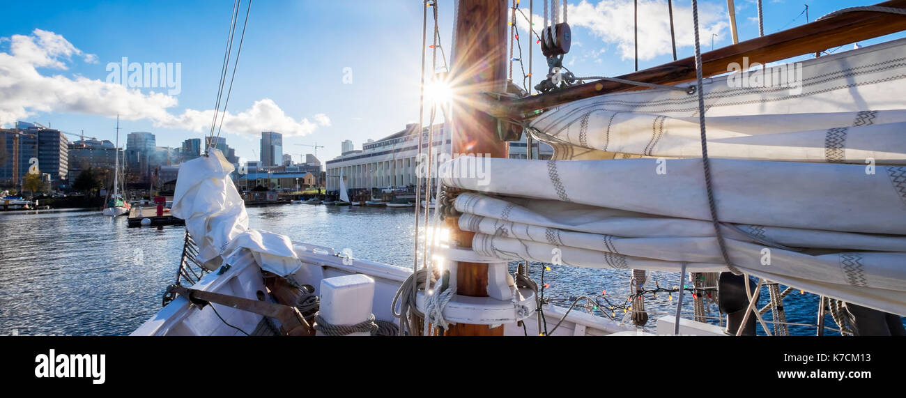 Seattle sailing on Lake Union in a vintage yacht. Sun flare, sunburst on the mast. Banner format - Stock Image