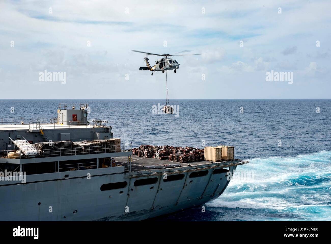 A MH-60 Sea Hawk transfers supplies from the fast combat support ship USNS Supply (T-AOE 6) - Stock Image