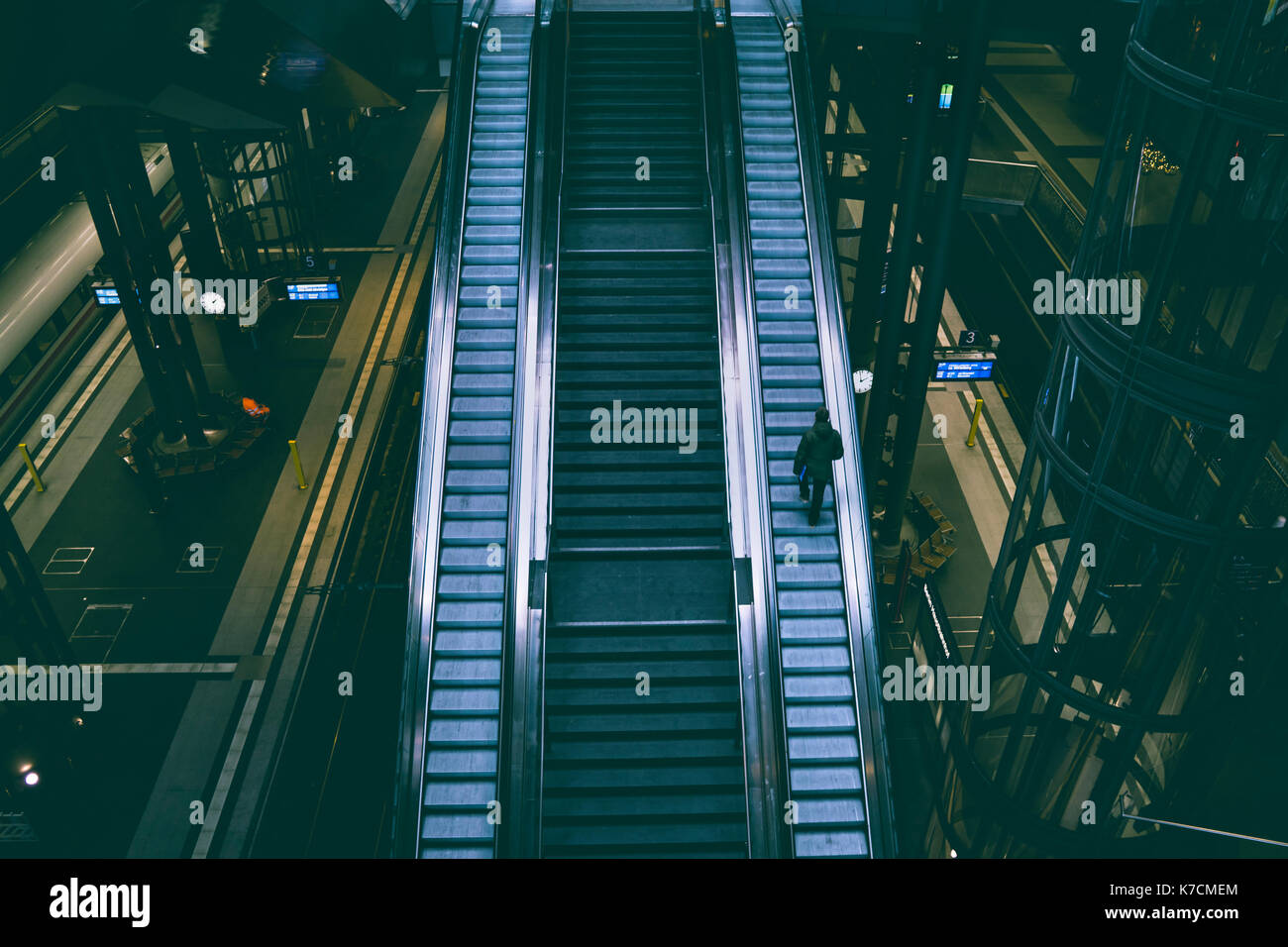 Lone traveller on escalator, central station. - Stock Image