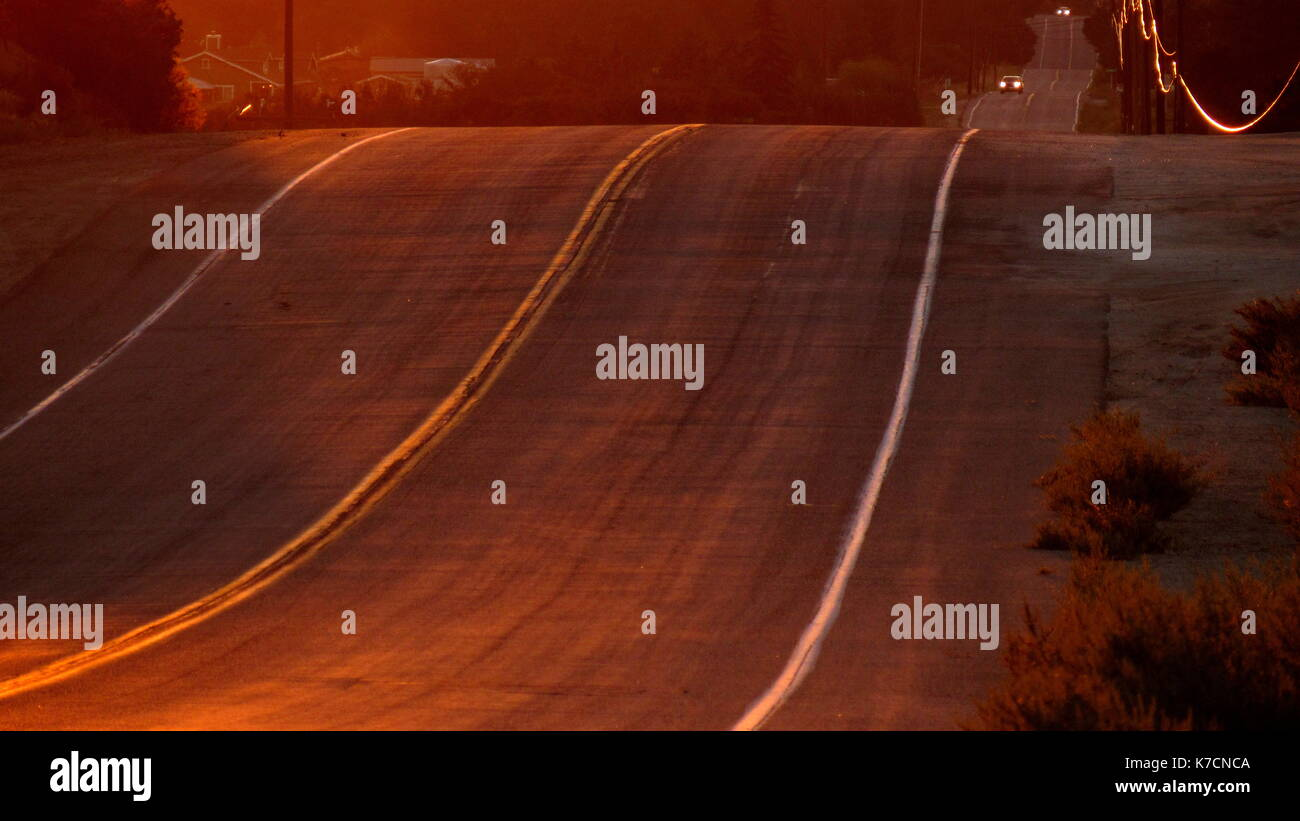 Curvy desert highway road going thought the Southern California golden state at sunset with a telephone line glinting with gold - Stock Image