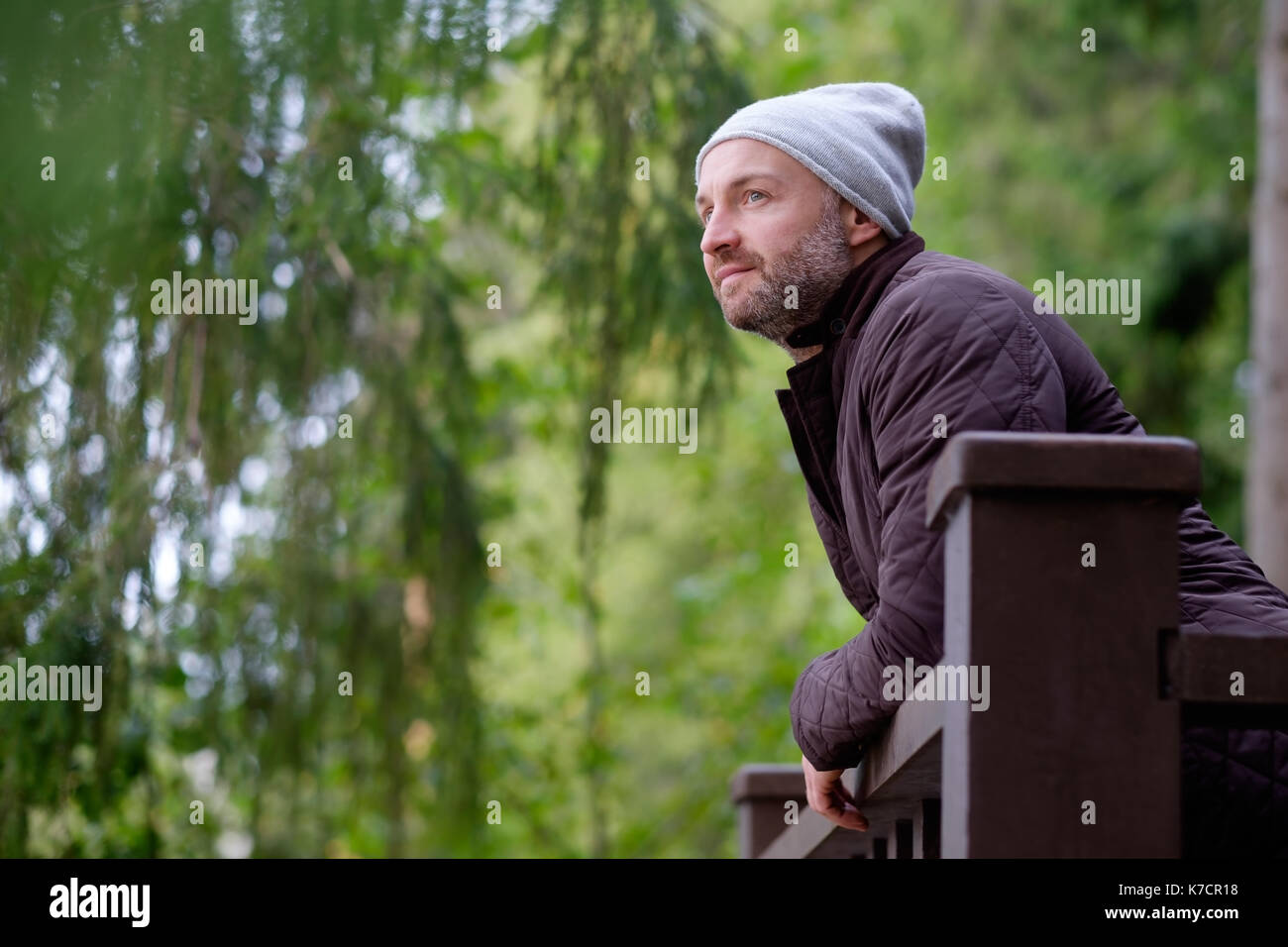 handsome mature man smiling in warm hat and jacket looking aside - Stock Image
