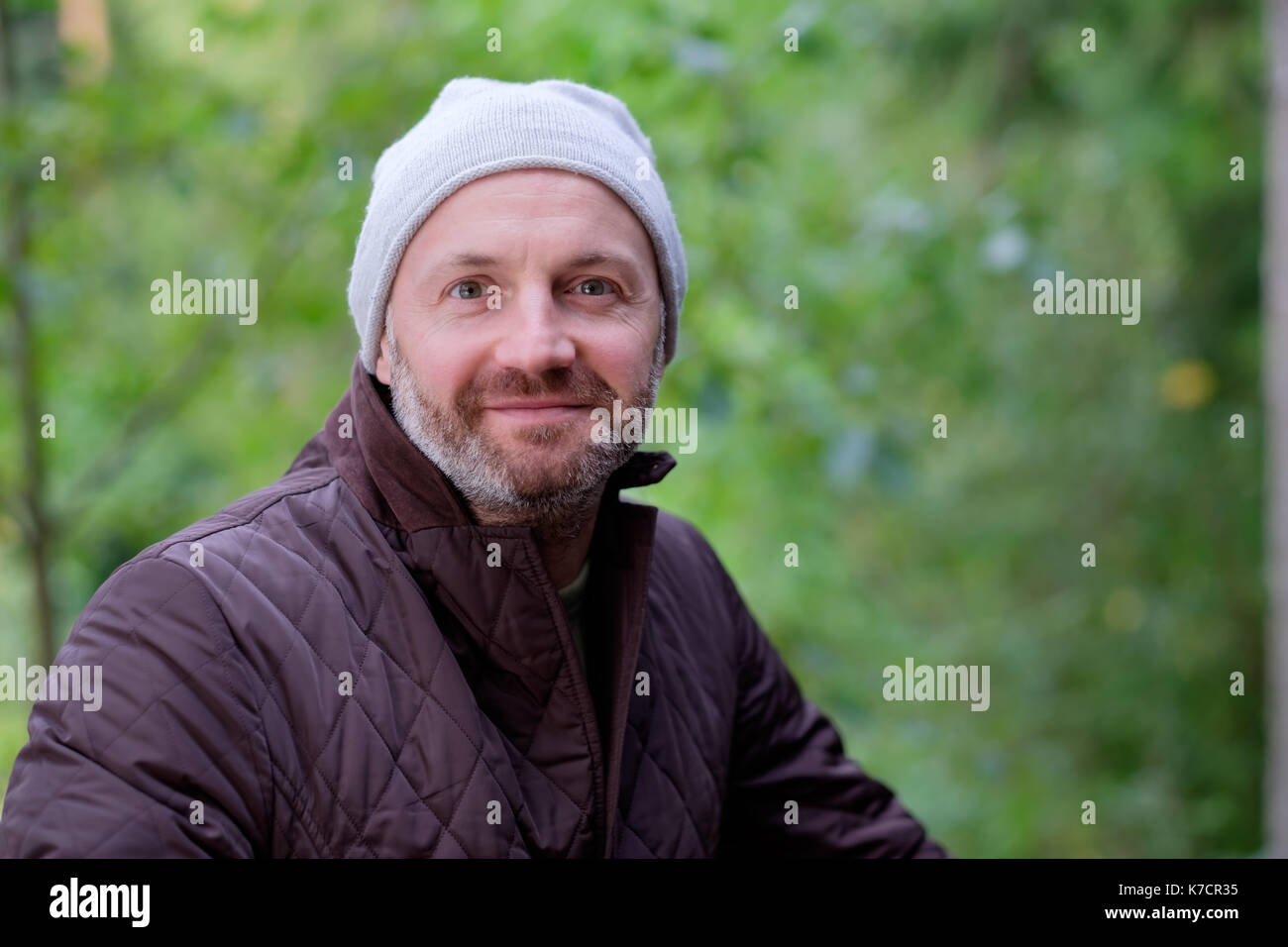 handsome mature man smiling in warm hat and jacket looking at camera - Stock Image
