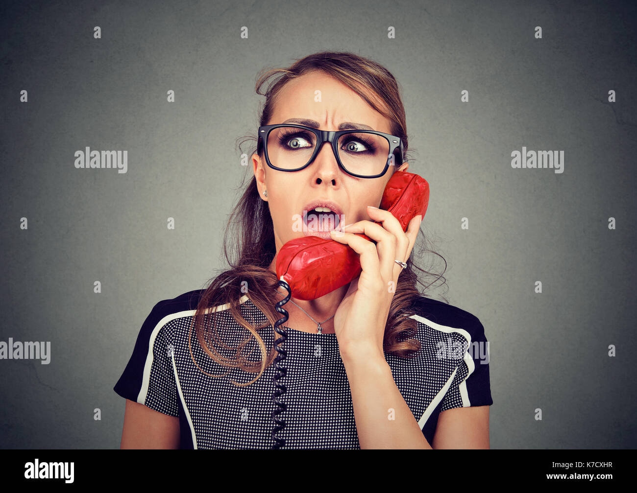 Shocked worried woman receiving bad news on the phone - Stock Image