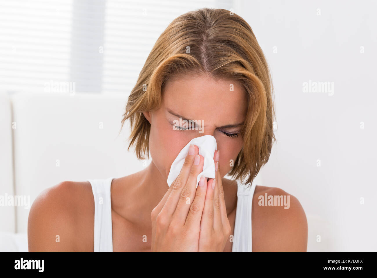 Portrait Of Young Woman Blowing Nose In Tissue Paper - Stock Image