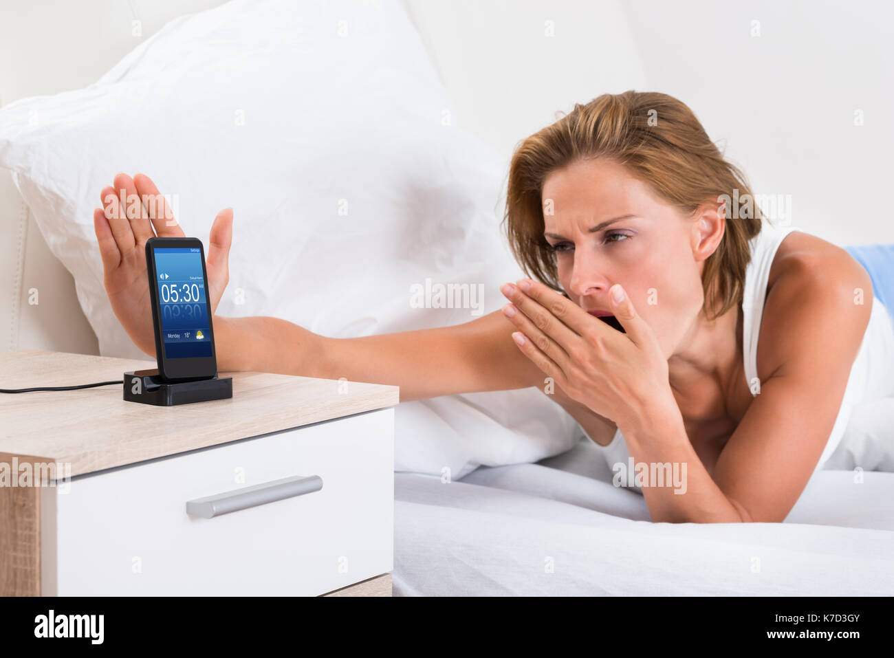 Young Woman Yawning While Snoozing Alarm On Mobile Phone - Stock Image