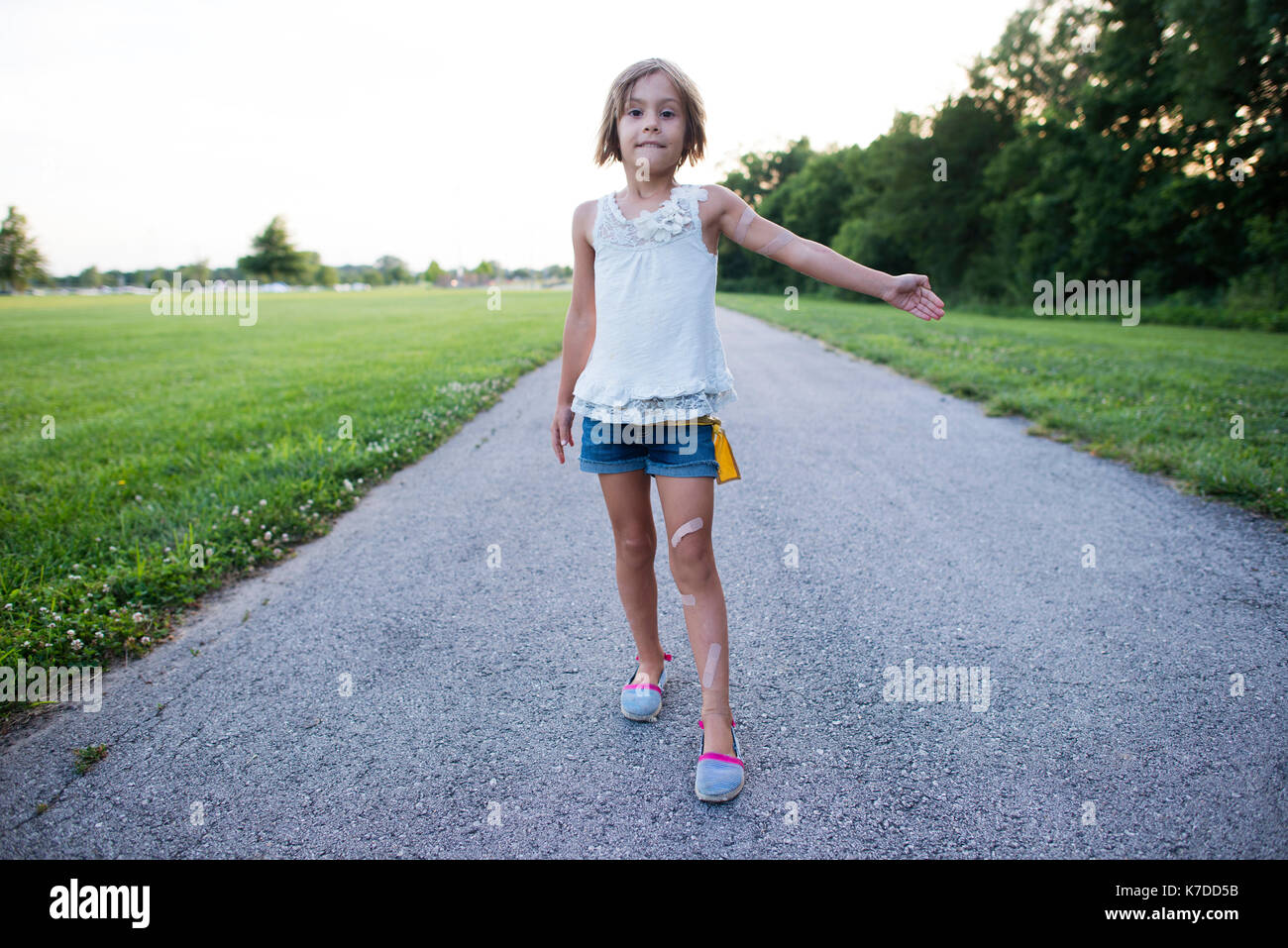 Portrait of girl showing bandages while standing on road against clear sky - Stock Image