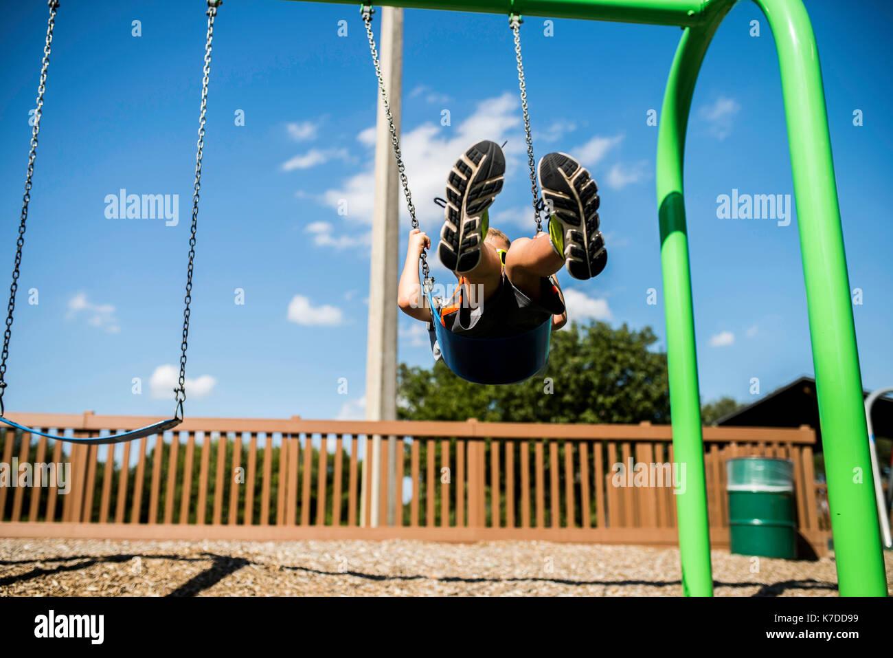 Boy swinging at playground during summer - Stock Image