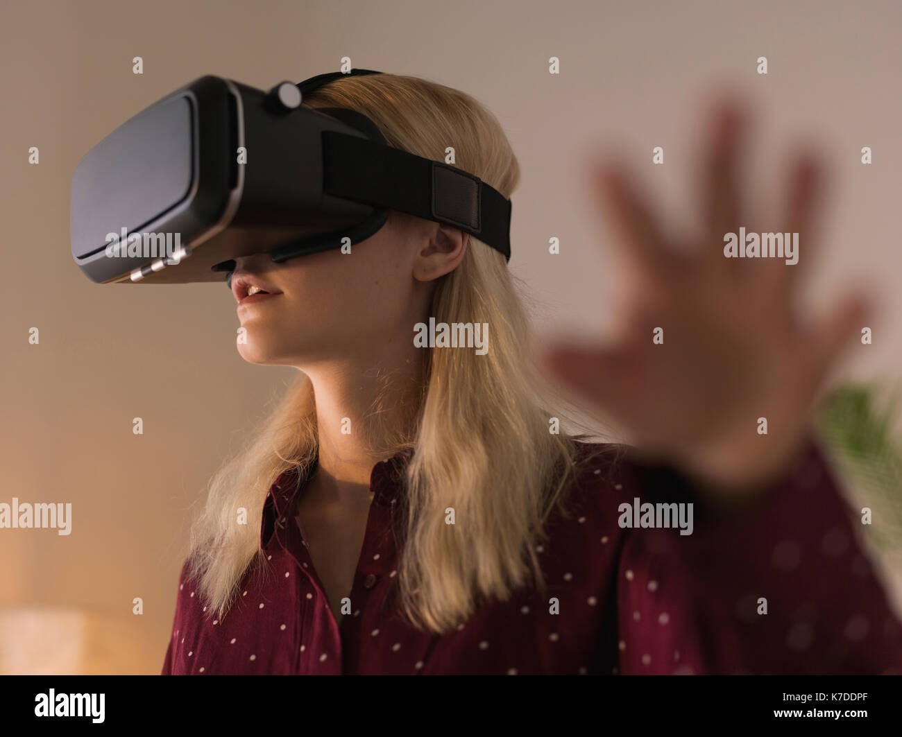Woman using virtual reality simulator at home - Stock Image
