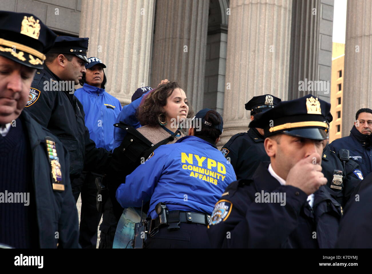 NYPD officers arrest a young woman as she attempts to stand on the steps of the New York County Supreme Court at Stock Photo