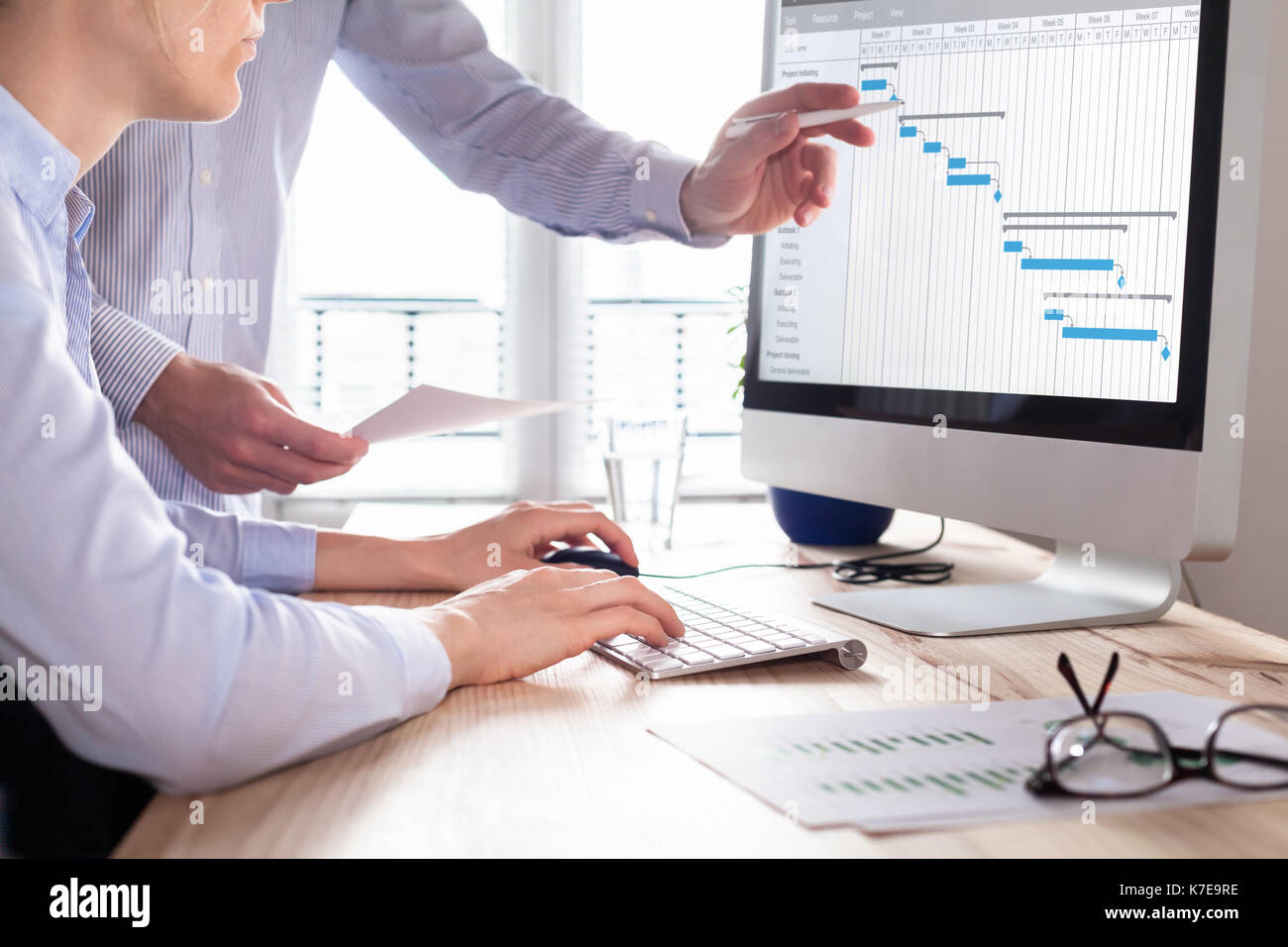 Project management team updating Gantt chart schedule or planning on computer, two business people in office - Stock Image