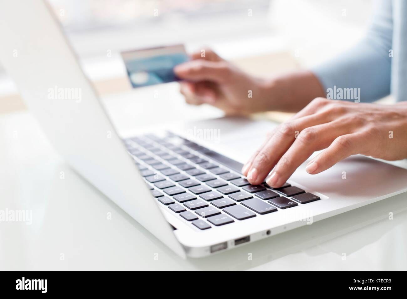 Woman using credit card and laptop. - Stock Image