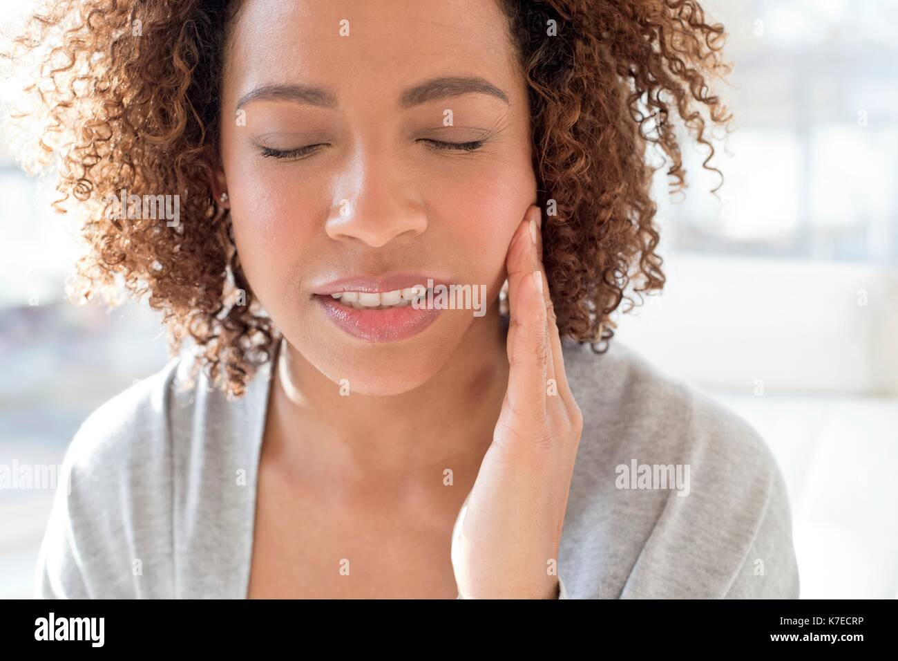 Portrait of mid adult woman touching face. - Stock Image