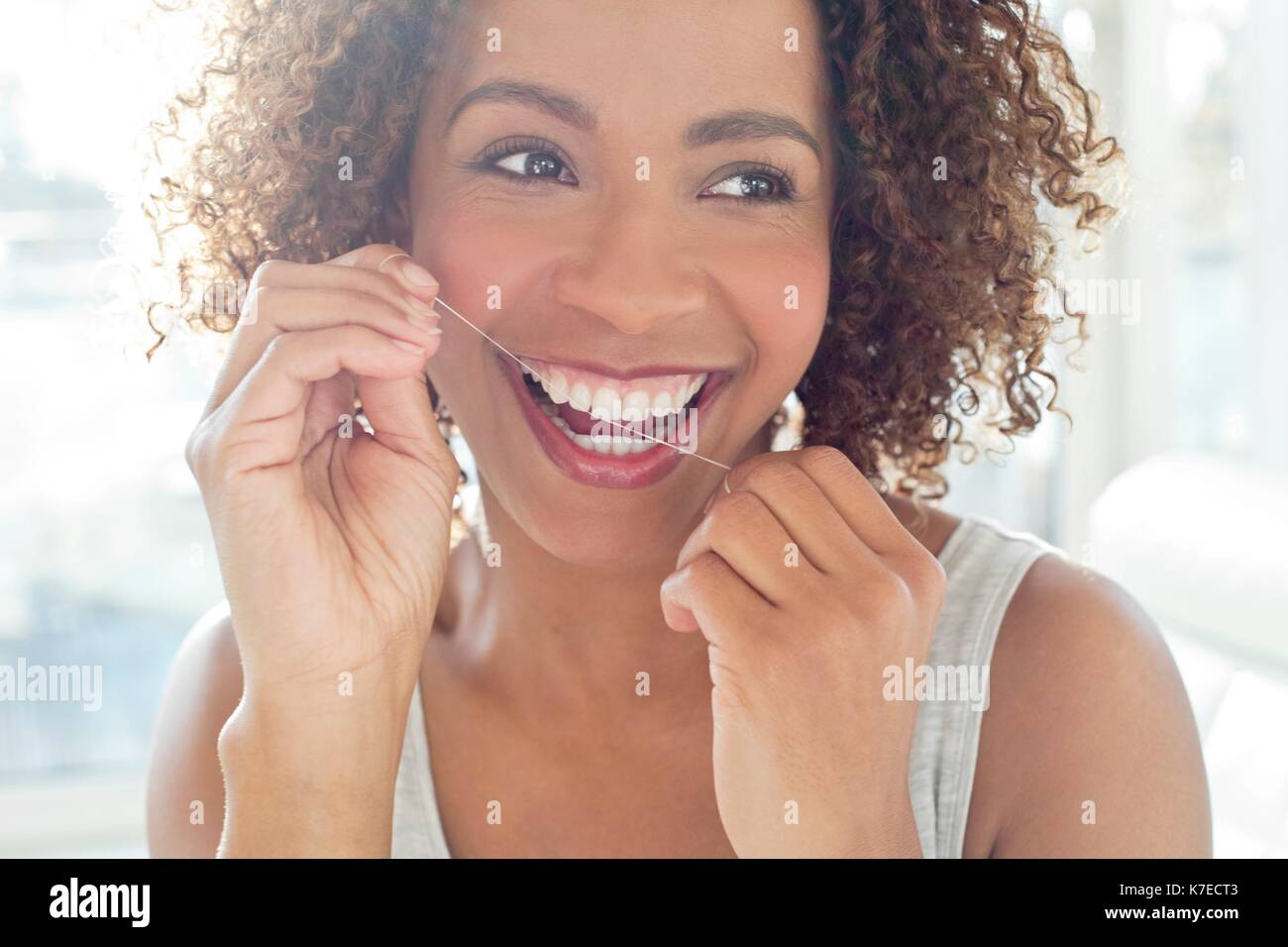 Portrait of mid adult woman flossing teeth. - Stock Image