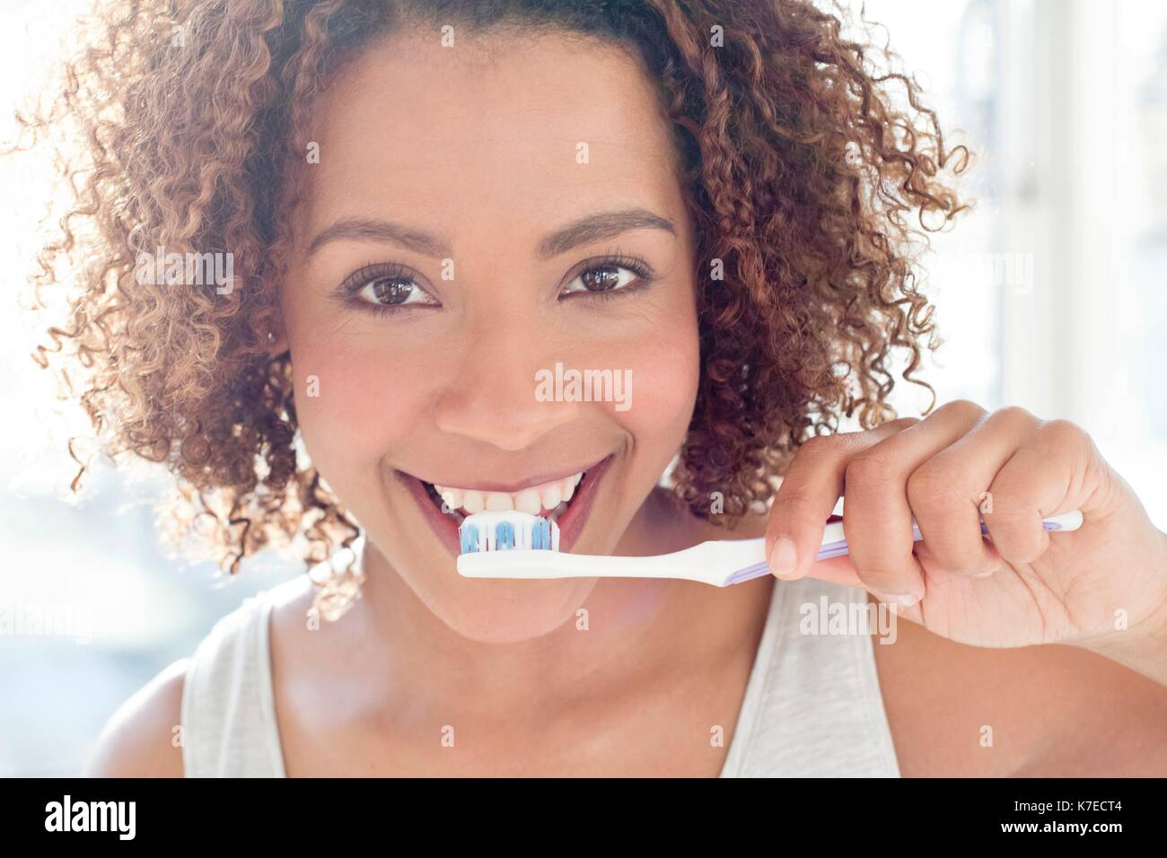 Portrait of mid adult woman brushing teeth. - Stock Image