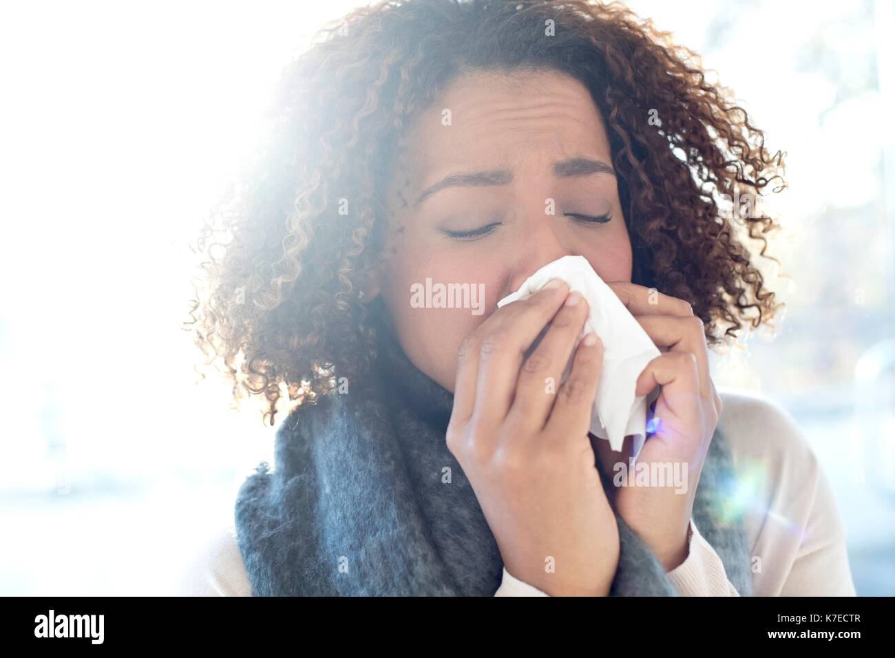 Mid adult woman blowing nose on tissue. - Stock Image