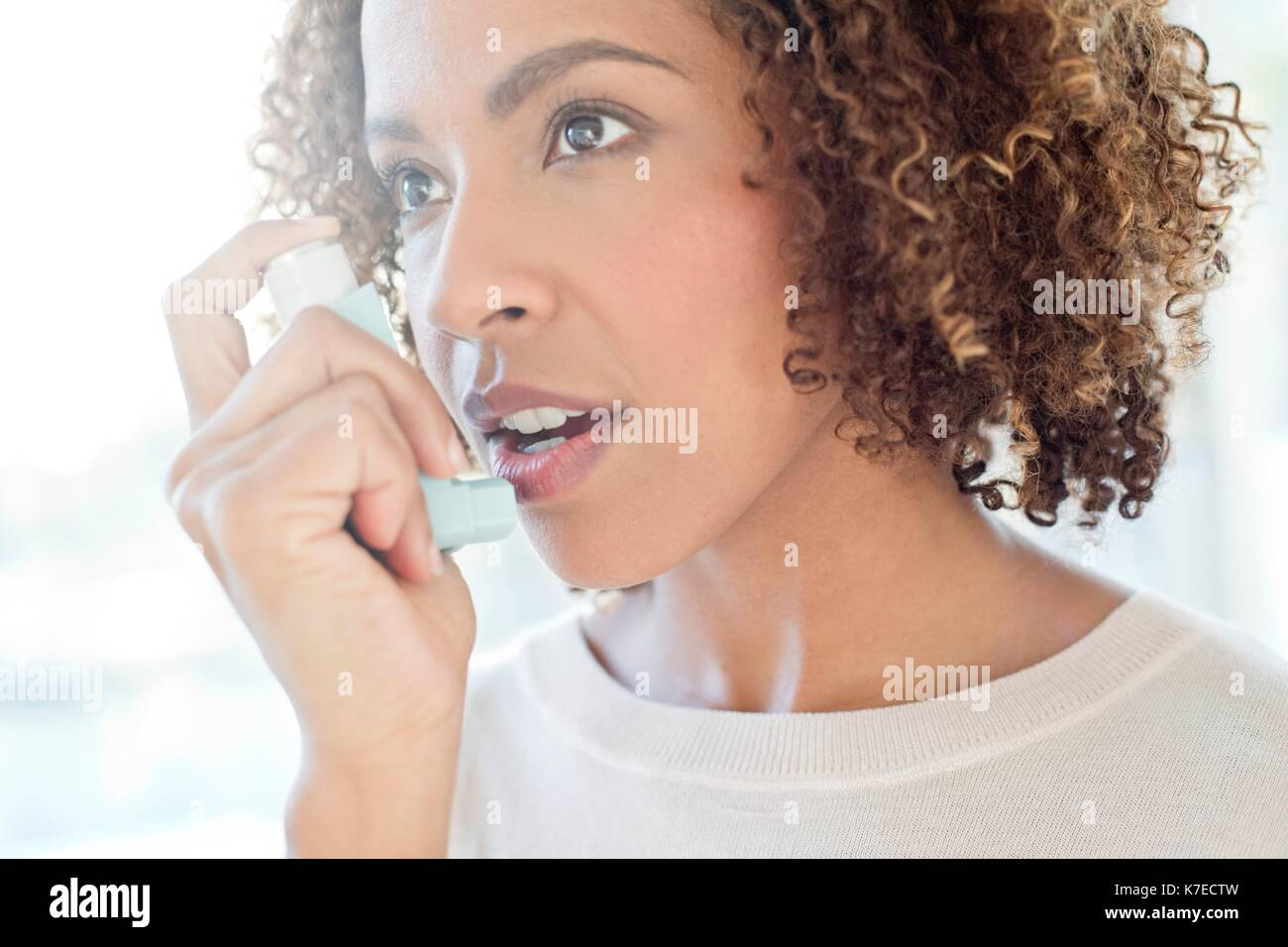 Mid adult woman using inhaler. - Stock Image