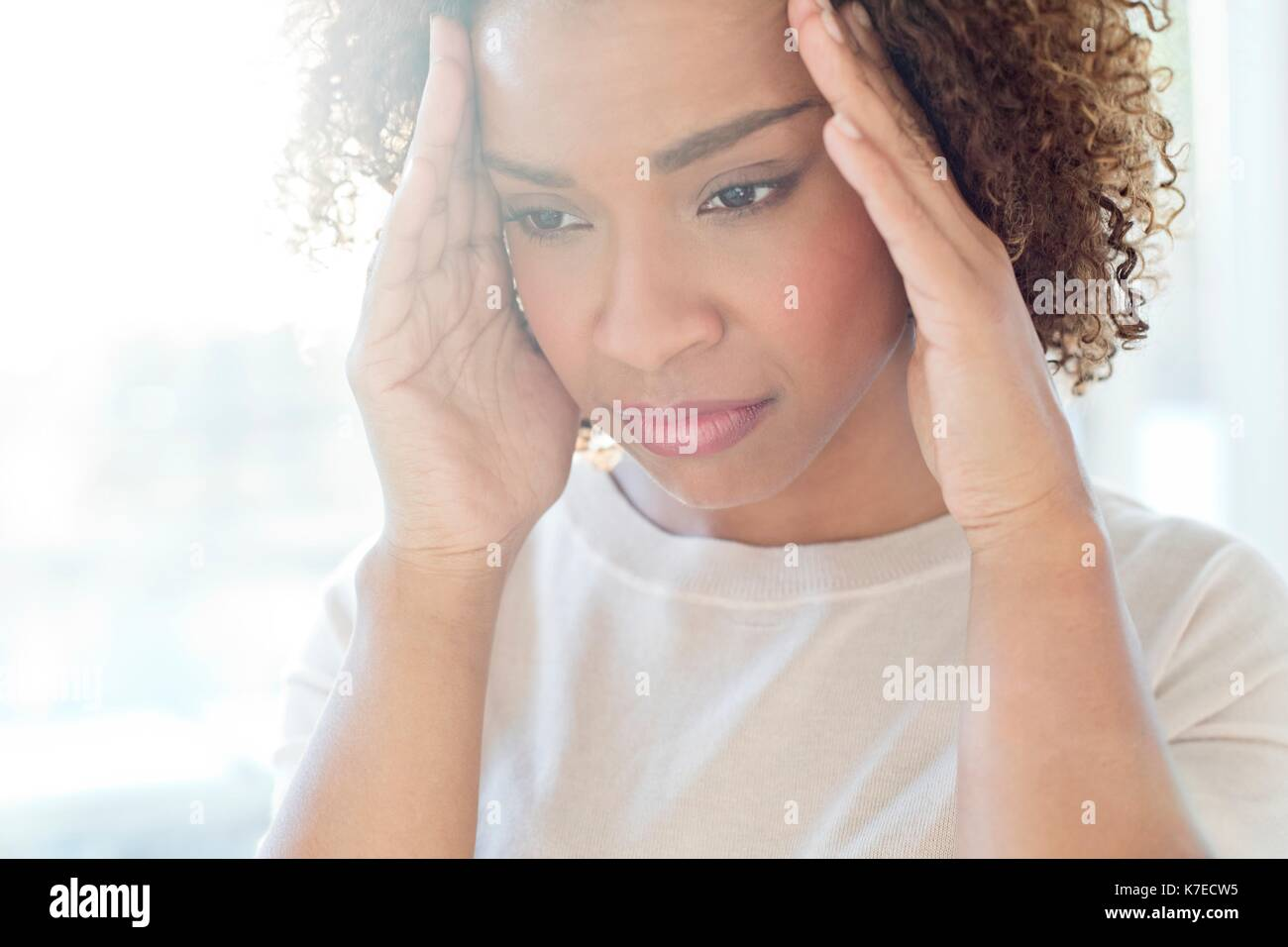 Mid adult woman touching her head. - Stock Image
