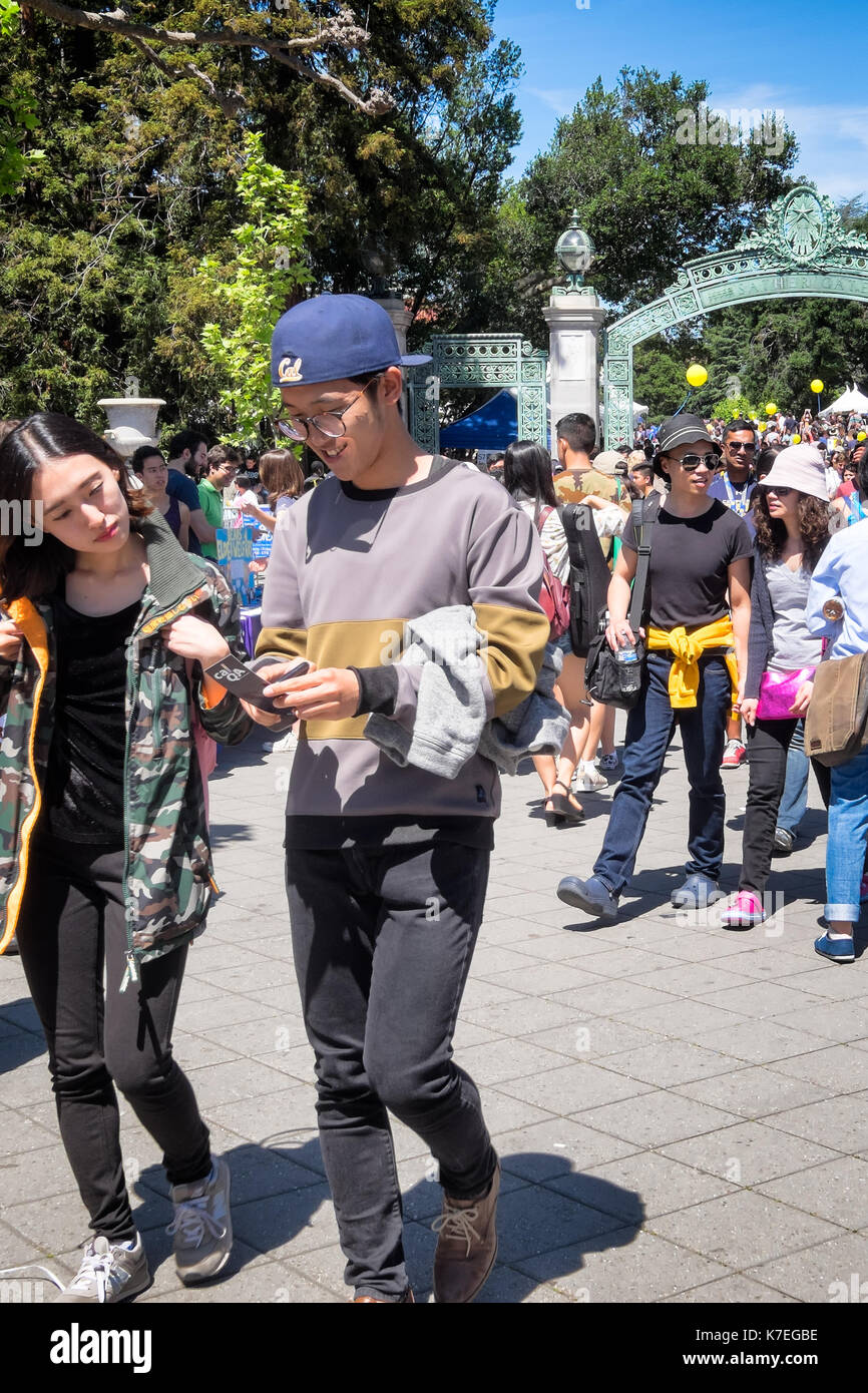 Crowds of students at the University of California Berkeley during a Spring open house known as Cal Day. Focus is on a couple in the foreground. - Stock Image