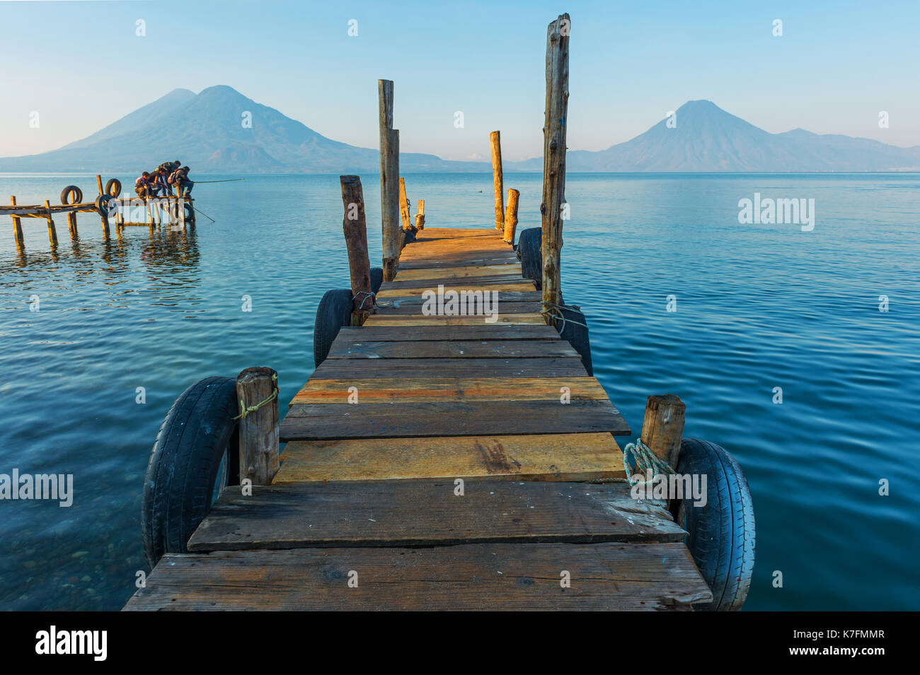 Young boys fishing on a pier by the Atitlan Lake at sunrise with volcano San Pedro in the background near Panajachel in Guatemala, Central America. - Stock Image