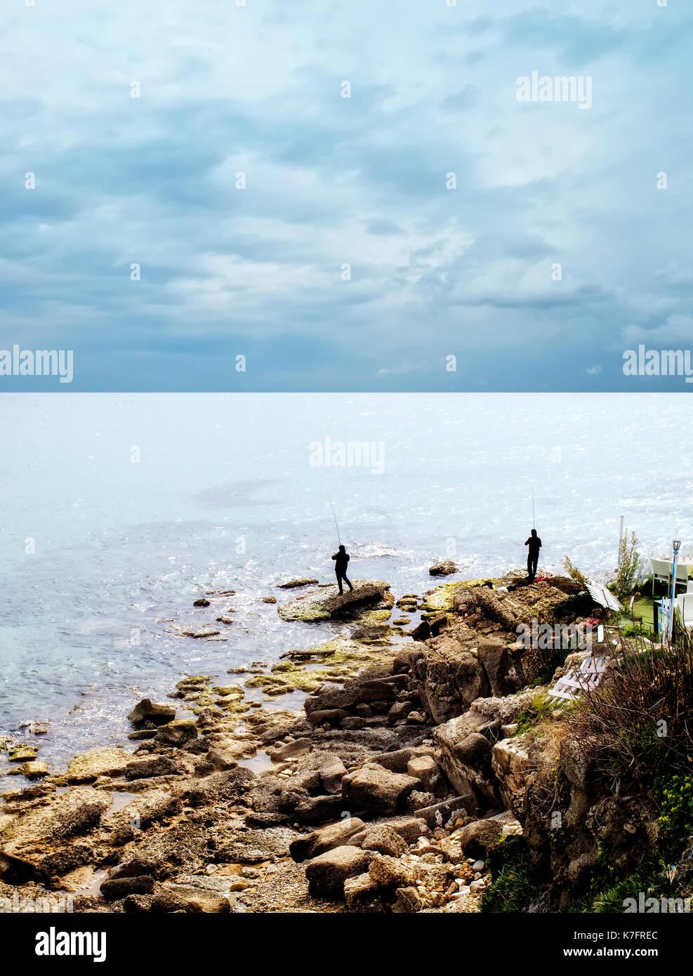 two fishermen sea fishing on rocky beach - Stock Image