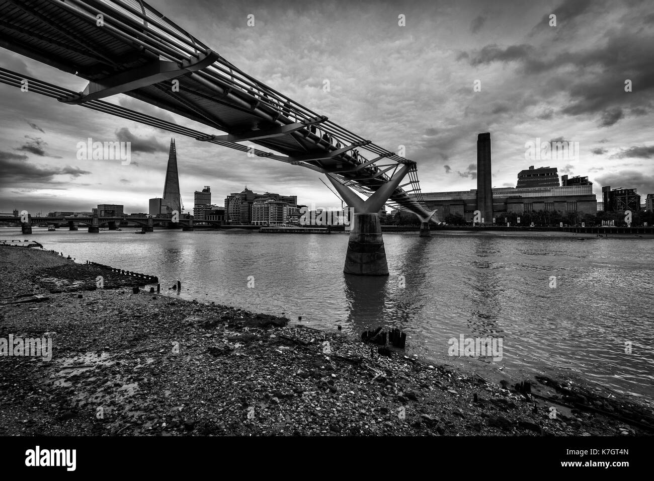 The Shard Building, Millennium Bridge and The Tate Modern Gallery on the River Thames at Low Tide. Stock Photo