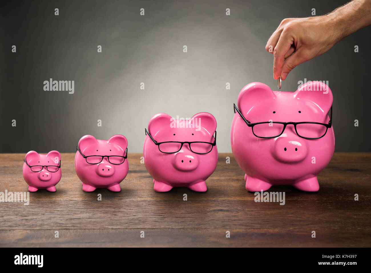 Close-up Of Person Hand Inserting Coin In Pink Piggybank On Table Stock Photo