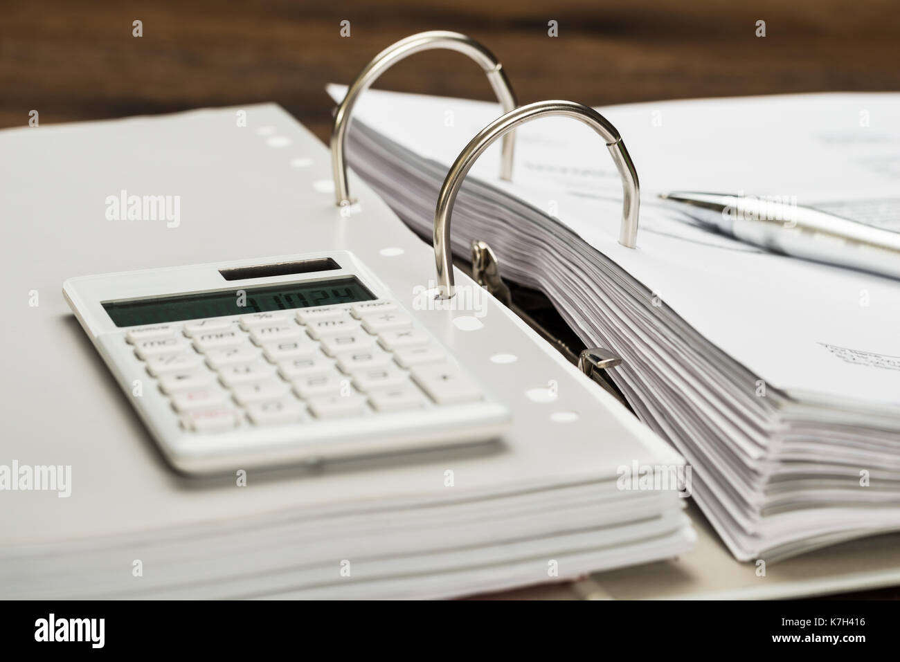 Close-up Of Invoice With Calculator And Pen On Desk Stock Photo
