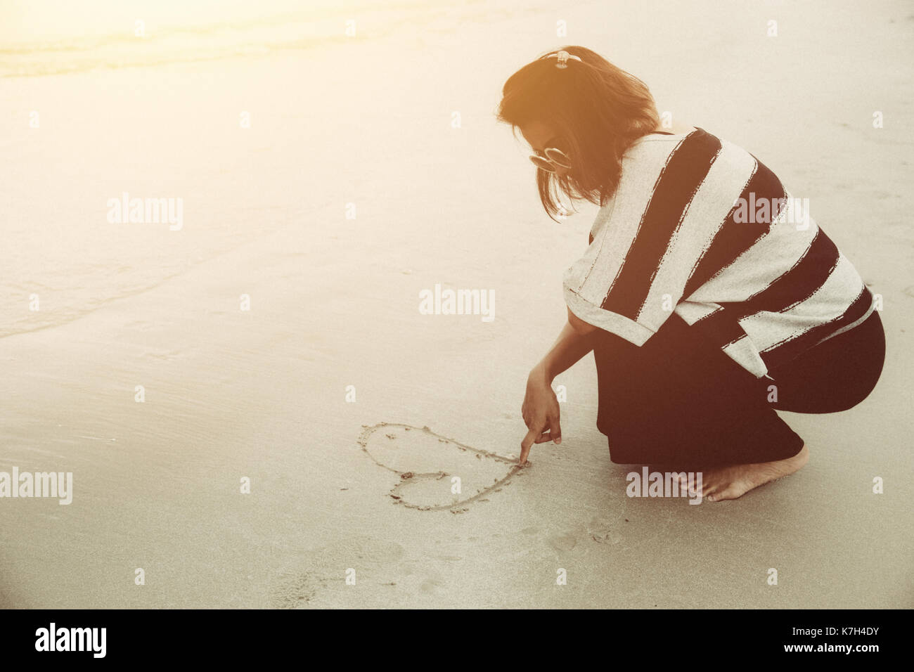Single broken heart girl concept. Hipster alone women drawing one heart with her finger on the sea beach vintage warm color tone. - Stock Image