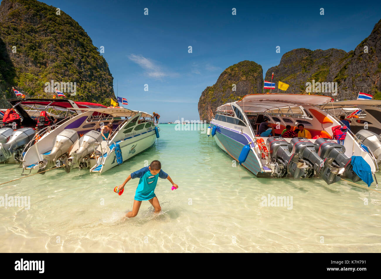 Boy plays between tourist boats lined up at Maya Bay, Ko Phi Phi Lee Island, Thailand. - Stock Image
