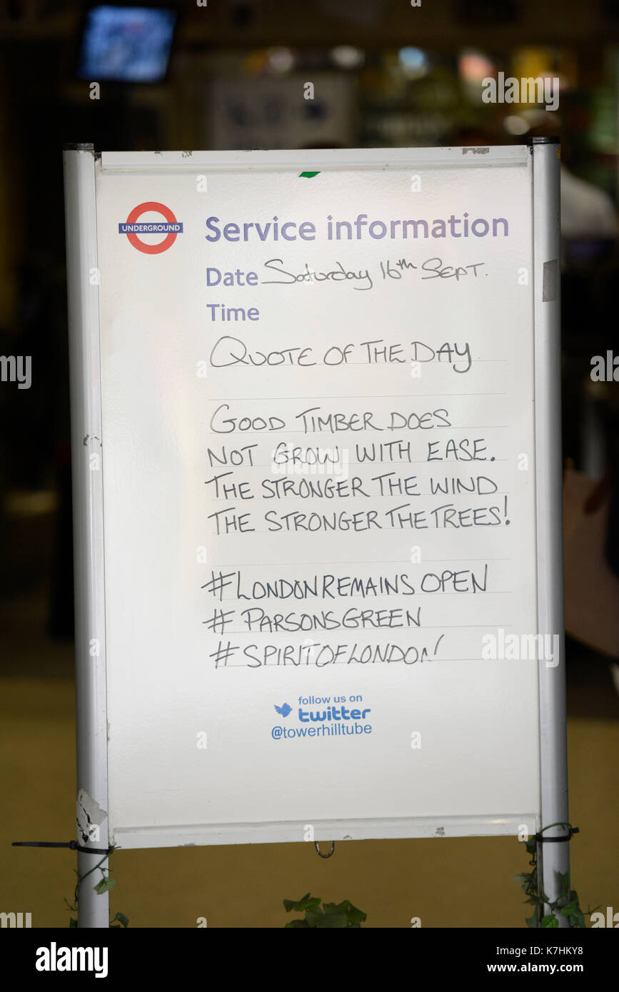 People continue to use the London Underground. Staff at Tower Hill display stoic message - Stock Image