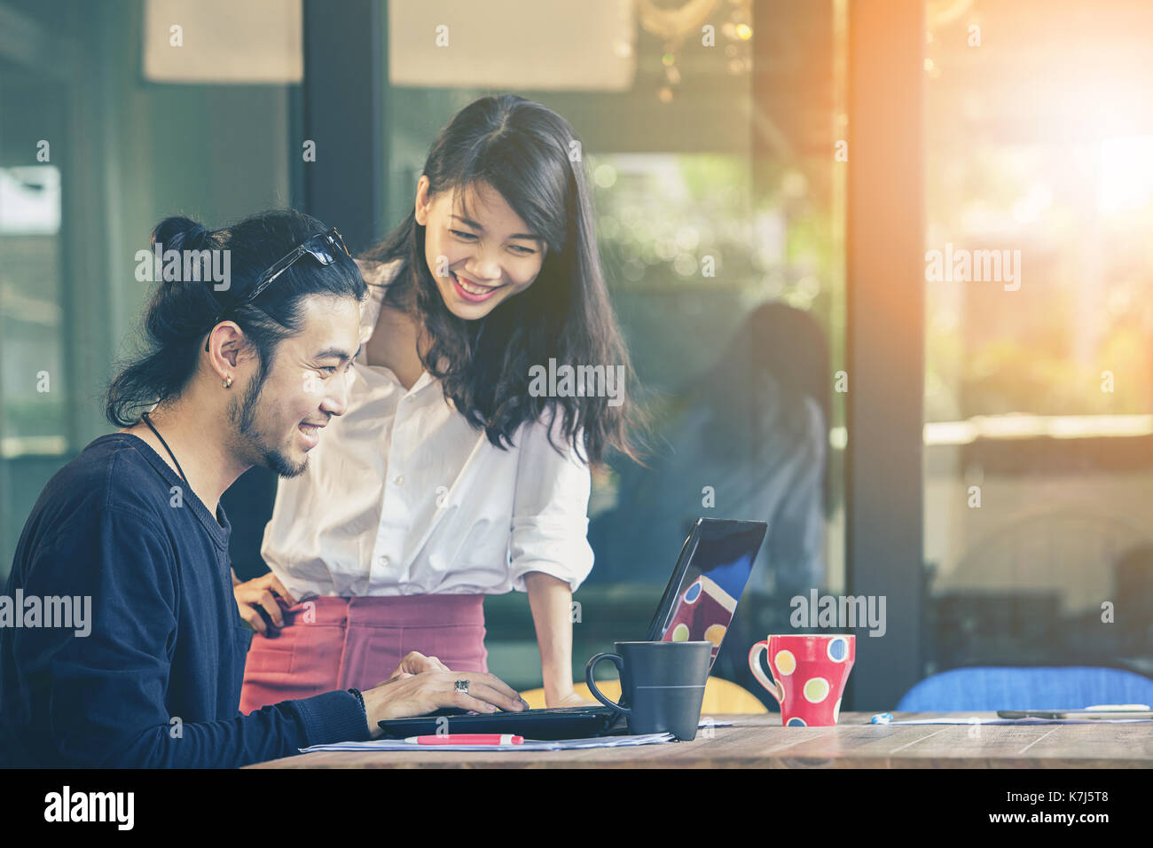 happiness emotion of asian younger man and woman ,freelance team working with computer laptop in home office - Stock Image