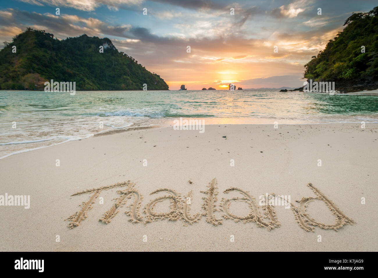 'Thailand' written in the sand on the beach at Tup Island with the sunset over the sea in the background, Thailand. - Stock Image