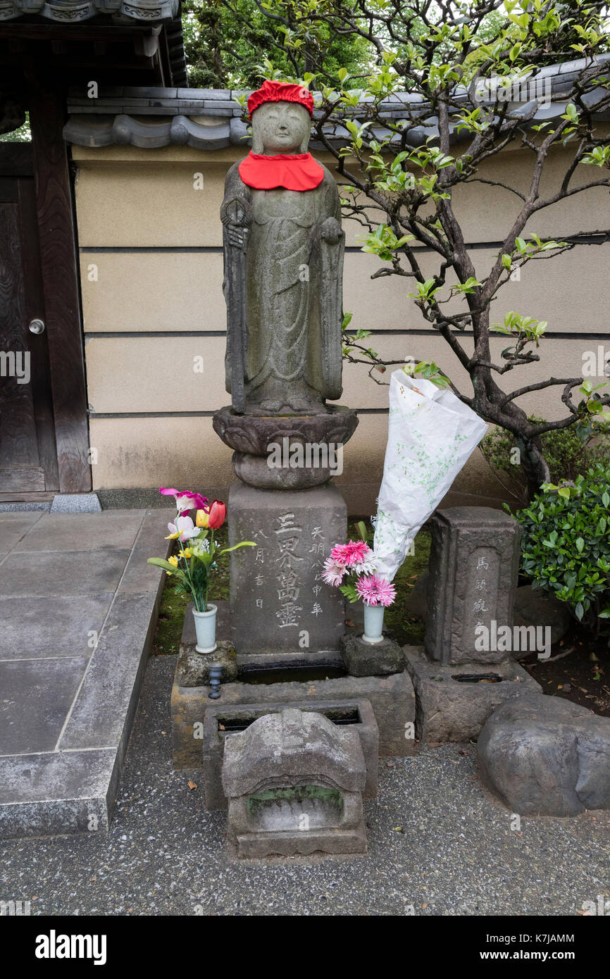 Tokyo, Japan -  May 15, 2017: Peaceful stone religious Jizo statue with red hat and honoured with fresh flowers - Stock Image