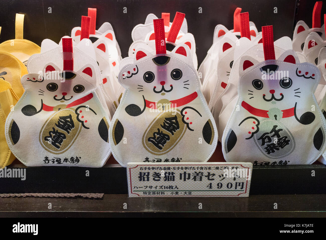 Kyoto, Japan -  May 17, 2017:  Traditional happy cat, maneki-neko, sac filled with sweets on the Nishiki market as a souvenir - Stock Image