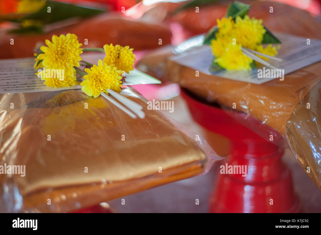 Gifts, bowls and robes at Wat Chedi Luang Temple in Chiang Mai, Thailand - Stock Image
