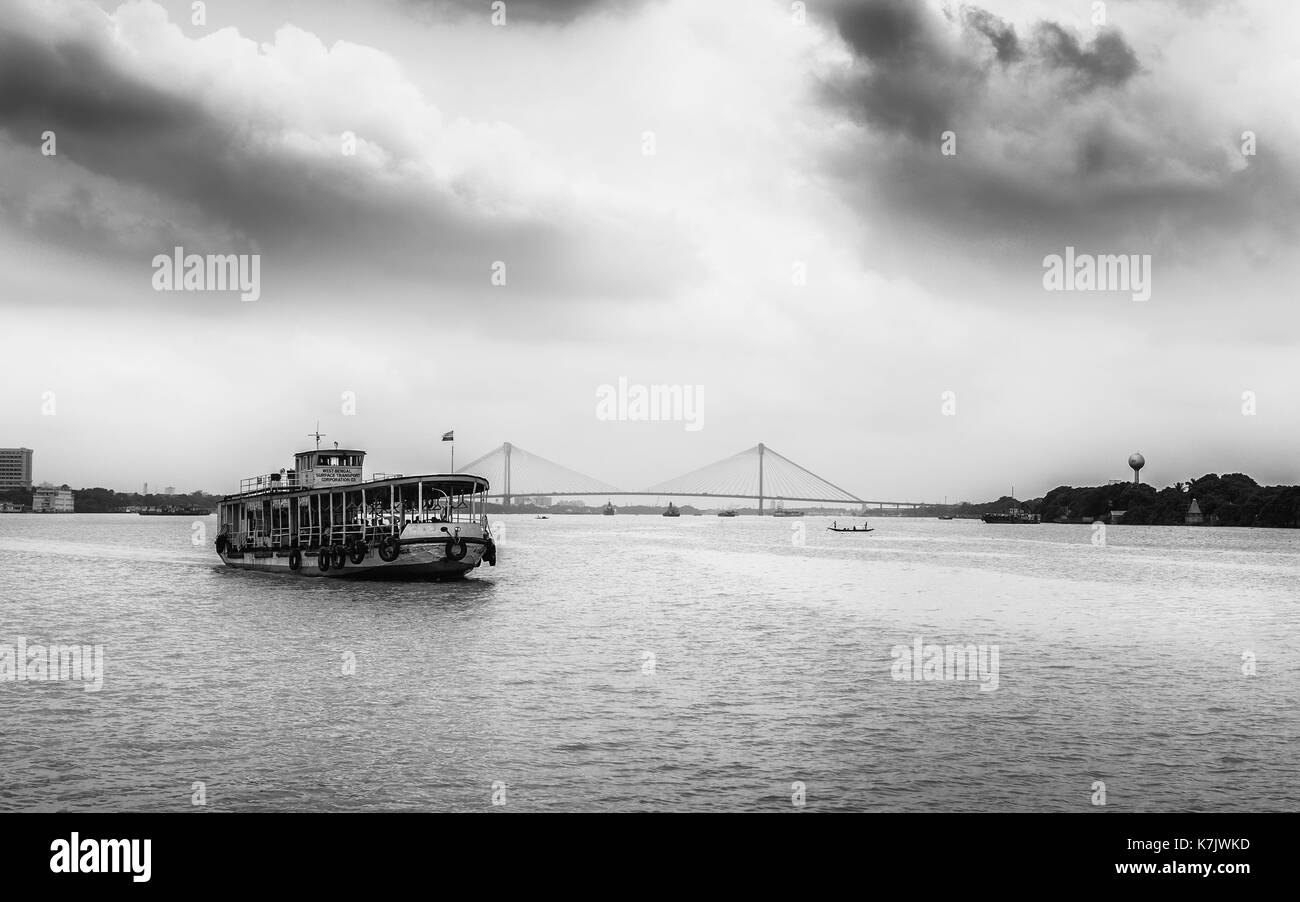 Public ferry crosses Hooghly river on overcast monsoon morning with view of new Howrah bridge in background in Kolkata, India. - Stock Image