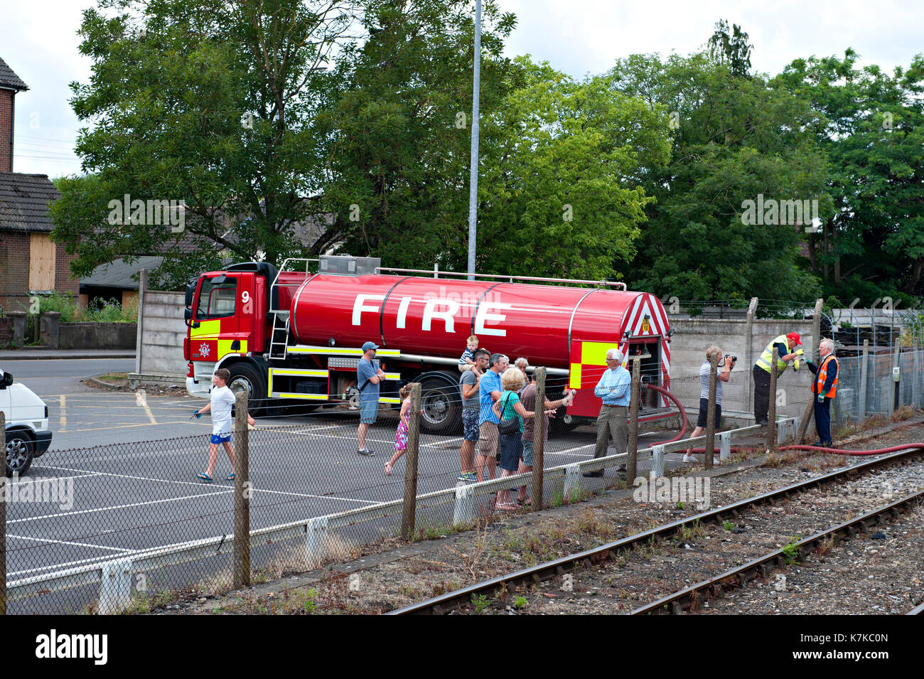 A fire tender providing water for a steam locomotive at a water stop during a special charter service - Stock Image