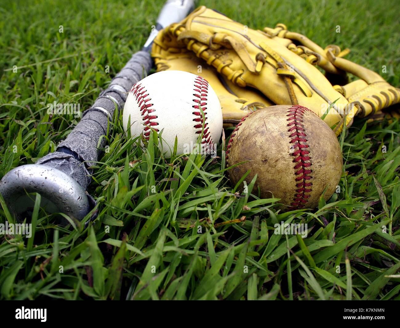 Photo of a baseball gloves, baseball and a baseball bat on the grass - Stock Image